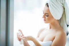Piękna kobieta używa skóry opieki produkt, moisturizer, płukanka lub Skincare bierze opiekę jej sucha cera, fotografia royalty free
