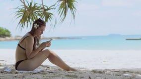 Piękna kobieta używa smartphone przy plażą tropikalna wyspa zbiory