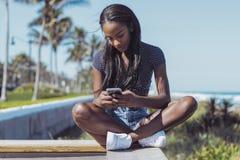 Piękna kobieta używa telefon na ogrodzeniu Obraz Stock