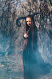 Piękna kobieta ubierał jako czarodziejska czarownica w deszczowu z rogami dla Halloween i Obraz Stock