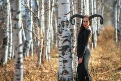 Piękna kobieta ubierał jako czarodziejska czarownica w deszczowu z rogami dla Halloween i Zdjęcia Stock