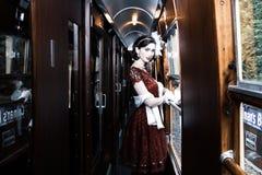Piękna kobieta ubierał w czerwonej herbacianej rocznik herbaty sukni na lokomotywa pociągu obrazy royalty free