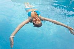 Piękna kobieta unosi się w pływackim basenie patrzeje kamera Obrazy Stock