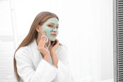 Piękna kobieta usuwa domowej roboty gliny maskę od jej twarzy fotografia stock