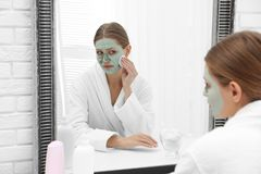 Piękna kobieta usuwa domowej roboty gliny maskę od jej twarzy przy lustrem zdjęcie royalty free