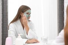 Piękna kobieta usuwa domowej roboty gliny maskę od twarzy przy lustrem indoors obraz royalty free