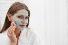 Piękna kobieta usuwa gliny maskę od jej twarzy obraz stock