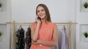 Piękna kobieta w ładnej sukni opowiada na telefonie sklepowymi stojakami zbiory wideo