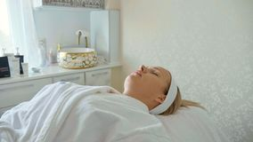 Piękna kobieta w bathrobe lying on the beach i czekanie opieki twarzowej procedurze przy zdroju salonem zdjęcia stock