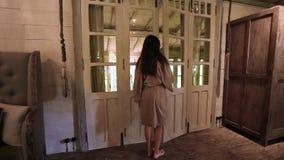 Piękna kobieta w bathrobe otwiera drzwi łazienka Rocznika pokój i ćmi światło zbiory