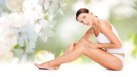 Piękna kobieta w bawełnianych bielizny macania nogach fotografia stock