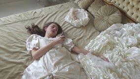 Piękna kobieta w białego rocznika balowym kostiumowym lying on the beach na ogromnym złotym łóżku z piórkowym fan i kapeluszem po zdjęcie wideo