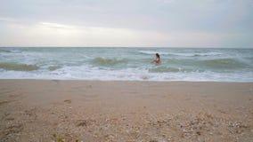 Piękna kobieta w białej swimsuit zabawie na fala w morzu w czasie burza zbiory wideo