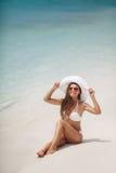 Piękna kobieta w białym kapeluszu na plaży i bikini Obraz Royalty Free