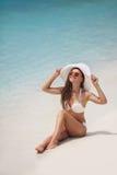 Piękna kobieta w białym kapeluszu na plaży i bikini Obraz Stock
