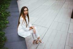 Piękna kobieta w białym kostiumu siedzi outdoors w podwórku Fotografia Royalty Free