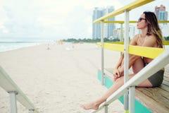 Piękna kobieta w bikini obsiadaniu przy ratownik stacją, Miami Obrazy Royalty Free