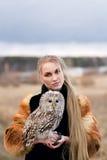 Piękna kobieta w czarnej sukni z sową na jego ręce Blondynka trzyma sowy z długie włosy w naturze Romantyczna delikatna dziewczyn zdjęcie royalty free