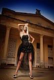 Piękna kobieta w czerni smokingowy pozować plenerowy. Seksowna kobieta w eleganckiej retro scenie. Elegancka kobieta przed kasztel Fotografia Stock