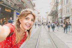 Piękna kobieta w czerwieni sukni bierze selfie przy Istiklal ulicą zdjęcie royalty free