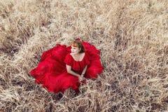 Piękna kobieta w czerwieni sukni obsiadaniu na jęczmiennym polu Fotografia Stock