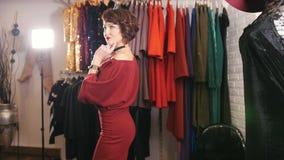 Piękna kobieta w czerwonej wieczór sukni pozuje dla fotografa w butik sala wystawowej zbiory