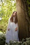 Piękna kobieta w długiej biel sukni pozyci w lesie Obraz Stock