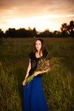 Piękna kobieta w długim smokingowym mienie bukiecie dzicy kwiaty Zdjęcie Royalty Free