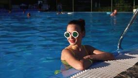 Piękna kobieta w eleganckich szkłach jest w basenie, ona cieszy się ciepłego dzień zbiory