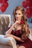 Piękna kobieta w eleganckiej plenerowej sukni pozuje samotnie, siedzący w krześle obraz royalty free