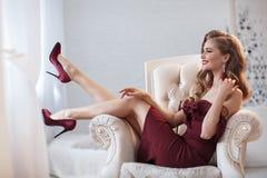Piękna kobieta w eleganckiej plenerowej sukni pozuje samotnie, siedzący w krześle fotografia stock