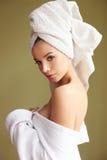Piękna kobieta w kąpielowym kontuszu z ręcznikiem na jej kierowniczym przyglądającym zamyśleniu Zdjęcie Royalty Free