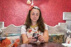 Piękna kobieta w kawiarni używa smartphone Piękna młoda kobieta używa smartphone w kawiarni podczas gdy siedzący Pomyślny femal Obrazy Stock