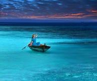 Piękna kobieta w kruchej łodzi w morza burzowych spojrzeniach przy horyzontem, mieć_nadzieja dla pomocy Zdjęcia Royalty Free