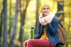 Piękna kobieta w lesie, termosie i filiżance jesieni, Obraz Stock