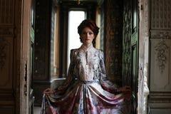 piękna kobieta w menchii smokingowy pozować w luksusowym pałac Fotografia Royalty Free