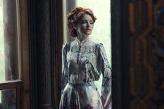 piękna kobieta w menchii smokingowy pozować w luksusowym pałac Obraz Royalty Free