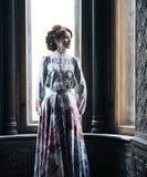 piękna kobieta w menchii smokingowy pozować w luksusowym pałac Obrazy Royalty Free
