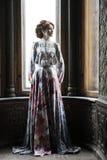 piękna kobieta w menchii smokingowy pozować w luksusowym pałac Zdjęcie Royalty Free