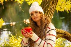 Piękna kobieta w pulowerze biel nakrętce i, kapelusz w spadku Spadku pojęcie - jesieni kobieta pije kawowego ot gorącej herbaty d fotografia stock