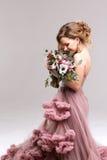 Piękna kobieta w różowej sukni pozuje z bukietem zdjęcia stock