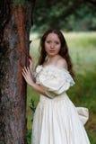 Piękna kobieta w rocznik sukni beżu Śliczna dziewczyna w długim smokingowym odprowadzeniu w sosnowym lesie styl królowa Obraz Stock