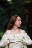 Piękna kobieta w rocznik sukni beżu Śliczny dziewczyna portret w długim smokingowym odprowadzeniu w sosnowym lesie styl królowa Obraz Stock