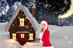 Piękna kobieta w Santa kostiumowej pozyci przeciw cyfrowo wytwarzającemu tłu Fotografia Royalty Free