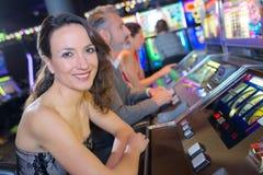 Piękna kobieta w smokingowym bawić się automat do gier zdjęcia stock