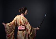 Piękna kobieta w tradycyjnym Japońskim kimonie z kataną Zdjęcia Royalty Free