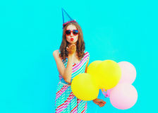 Piękna kobieta w urodzinowej nakrętce jest wysyła buziaka lotniczych chwyty lotniczy kolorowi balony na błękitnym tle Fotografia Royalty Free