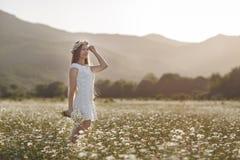 Piękna kobieta w wianku realów kwiaty z bukietem w polu białe stokrotki, Zdjęcie Stock