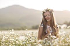 Piękna kobieta w wianku realów kwiaty z bukietem w polu białe stokrotki, Zdjęcia Stock