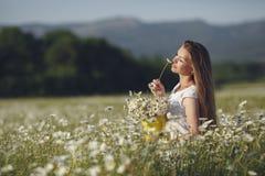 Piękna kobieta w wianku realów kwiaty z bukietem w polu białe stokrotki, Zdjęcie Royalty Free